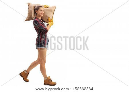 Full length profile shot of a female agricultural worker walking and carrying a burlap sack isolated on white background