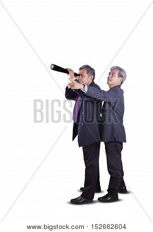 couples of asian business man spying by telescope lens for business strategy conceptual isolated white background