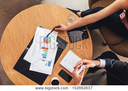 Two Business People Working With Charts Around Table