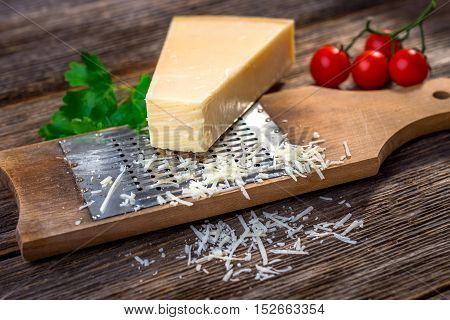 Grated Parmesan Cheese And  Grater On Wooden Background