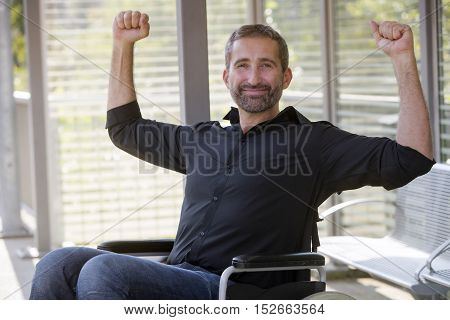 handsome man in wheelchair lifting his arms and looking very optimistic
