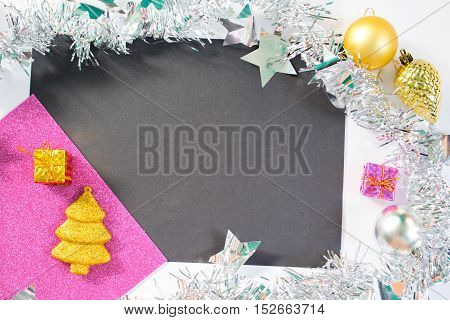 Christmas or New Year background with black pink and white paper. Blank place for text or mockup template. Silver garland wreath. Gold fir tree ornament. Photo background. Flat lay table composition
