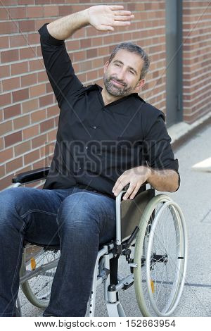 handsome man in wheelchair waving to somebody and smiles