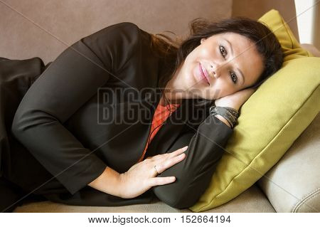 portrait of beautiful woman in her 40s lying on couch and smiling at camera