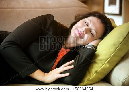 beautiful woman in her 40s lying on couch and sleeping