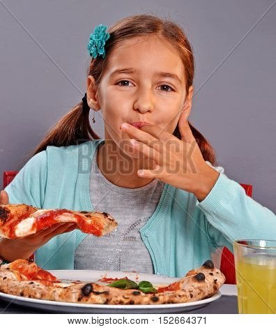 Hungry little girl sucking finger while eat margarita pizza in a restaurant.