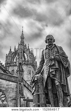 Statue of economist Adam Smith on the Royal Mile in Edinburgh capital of Scotland with St Giles cathedral in the background.