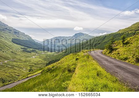 A winding mountain road in the highlands of Scotland.