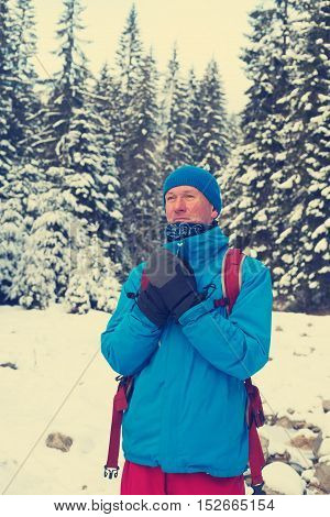 Hiker man warms his hands in mittens while he resting in the winter forest. Toned image