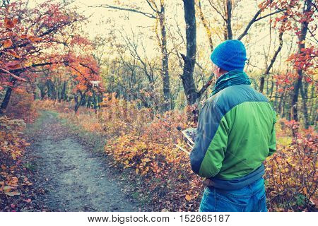 Man controls the drone in the autumn forest. Drone flies on the background of colorful autumn trees during sunset. Toned image.