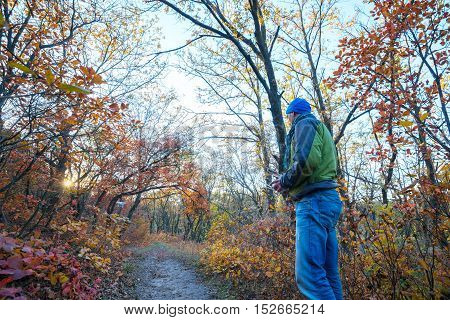Man controls the drone with remote controller in hands in the autumn forest. Drone flies on the background of colorful autumn trees during sunset. Wide angle. low point.