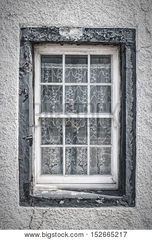 A window on the building of a house in Inveraray Scotland. What lurks behind the net curtains?