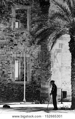 LARAPETRA CRETE - 02 MAY 2015: An old man stands in the shade of a palm tree next to the old Turkish mosque in Lerapetra on the Greek island of Crete.