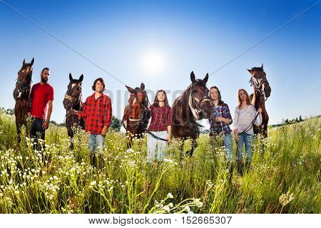Group of five happy young people with their horses in flowery meadows