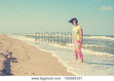 Joyful woman enjoying life on the beach at the windy weather. Toned image.