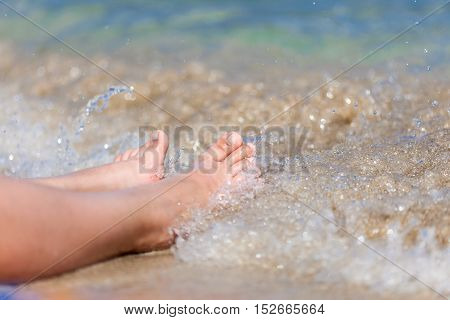 Legs of woman close-up on the beach in the water