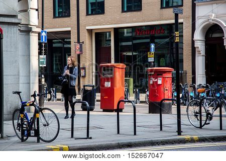 LONDON, UK - April 08, 2015: girl standing alone on the streets of London, there are a lot of bicycles