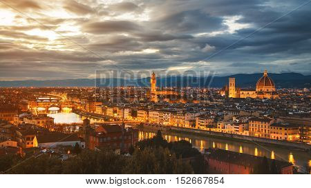 Aerial panoramic view of illuminated Florence Italy at night. All major landmarks - Cathedral Santa Maria Old Bridge and mountains at the background at sunset