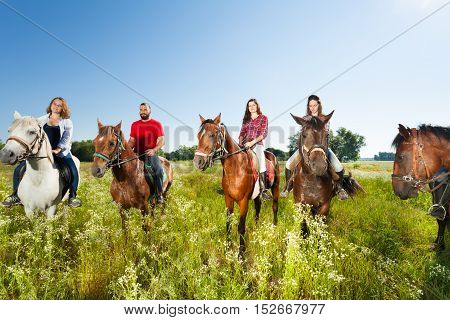 Big group of equestrians enjoy riding horses in summer field