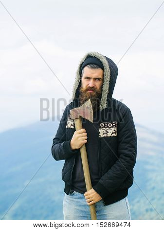 Handsome bearded hipster with thick beard and ruffled hair dressed on jacket with deer holding ax outdoor on beautiful landscape