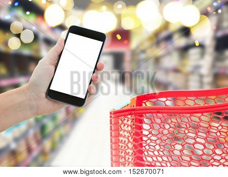 someones hand holding mobile smart phone with empty screen on supermarket blur background with red cart, business concept