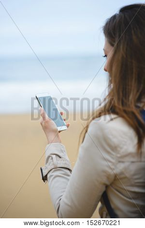 Woman Messaging On Smartphone On Winter At The Beach