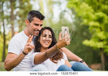 Young couple taking a selfie photo with smartphone camera at the park. Man and woman dating on summer or spring.