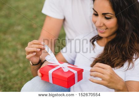 Loving couple celebrating birthday or anniversary with a present. Happy woman unwrapping gift red box.