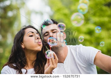 Young couple blowing bubbles. Man and woman dating and having fun at the park.