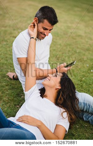 Loving young couple enjoying their love and leisure at the park. Happy relaxed girl caressing her boyfriend.