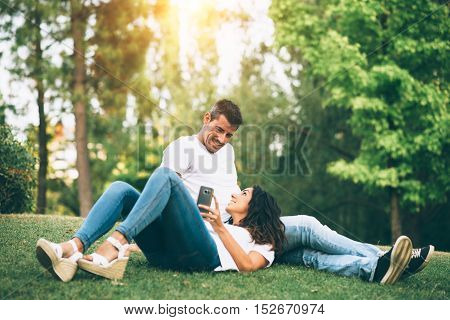 Young couple using smartphone and relaxing together outdoor. Man and woman enjoying summer or spring leisure and tranquility.