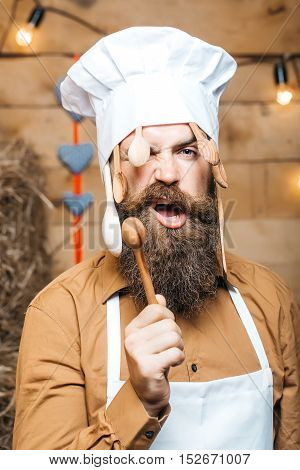 Brutal man chef cook or baker with beard and moustache in hat toque with wooden spoons and stirrers stands on straw bales on rustic background