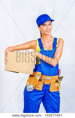 Beautiful happy woman moves to a new apartment, she carries a box with things. Repair, construction and mortgage concept.