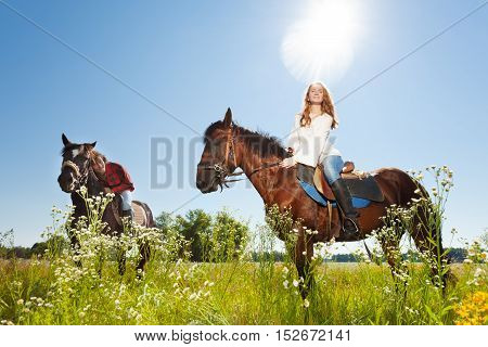 Portrait of happy young couple and their brown stallions, having rest in flowery meadows