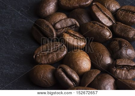 Coffee Beans Background Close Up. Roasted Coffee Beans On Dark Stone Surface.