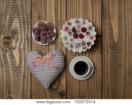 Decorative textile heart pillow tasty cookie fresh tasty berry raspberry and cup of aromatic coffee drink in white cup and saucer on wooden background