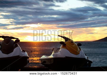 red scooters over dark twilight sky on beach with sea or ocean water on evening sunset natural background