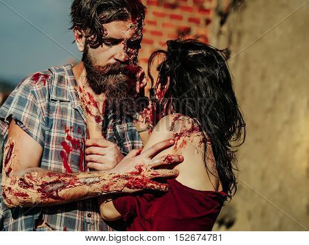 Bearded man zombie bloody hipster and creepy girl young woman with wounds and red blood outdoors on brick wall