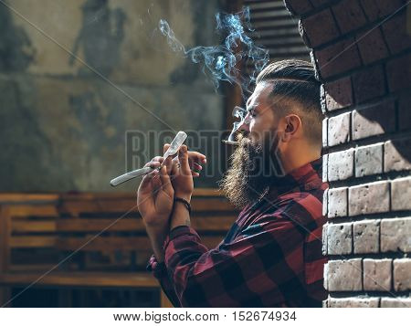 Young man hipster barber with handsome brutal face long beard and moustache smoking cigarette holding in hand and looking at cut throat razor equipment near brick arch background indoor