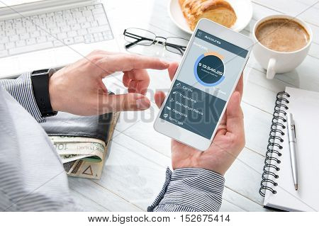 Businessman checks the account balance at breakfast