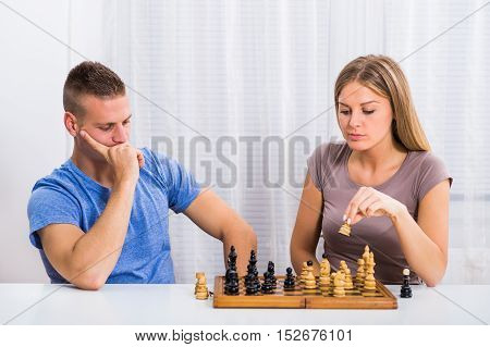 Young couple sitting at the table and playing chess.
