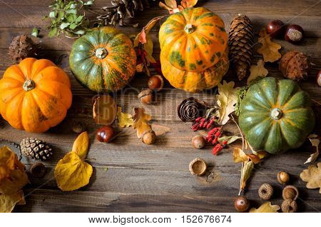 Autumn decorative pumpkins, fall leaves on a rustic wooden background, natural fall style decorations. Natural plenteous border background vintage mock up. Top view point.