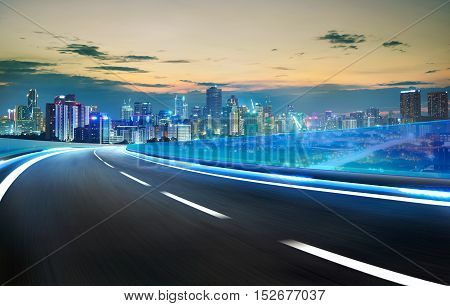 Blue neon light highway overpass motion blur with city skyline background night scene .
