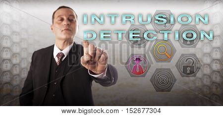Mature business manager with perky and confident look is activating INTRUSION DETECTION onscreen. Information technology and cybersecurity concept for identifying and monitoring network violations.