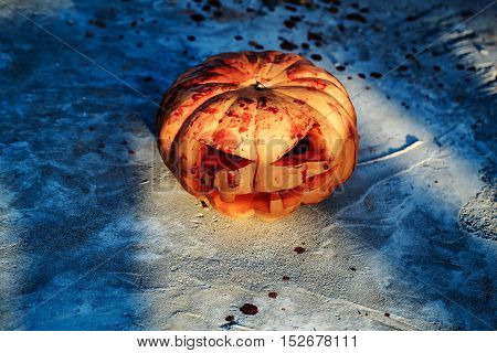 Halloween pumpkin traditional autumn holiday symbol bloody carved orange head with red blood drops outdoors on cement floor