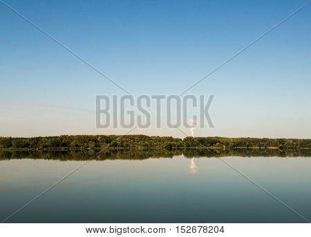 Lake landscape, a factory in distance. Lanscape image of a lake on a bright cloudless day with forest and a factory on lake's far end.
