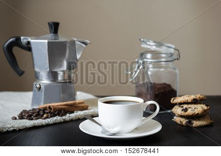 Black coffee with italian moka pot and cookies,front view. Front view of cup of black coffee, italian coffee pot on flax table-napkin and chocolate chip cookies on black vintage wood table indoors in natural light.