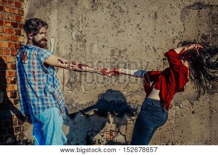 Halloween zombie couple of bearded man hipster or war soldier and bloody young woman with wounds and red blood hold hands outdoors on cement wall