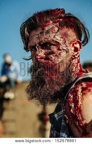 Bearded zombie man with beard halloween vampire or bloody war soldier with wounds and red blood outdoors on roof