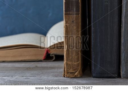 Close up stack of old books on a wooden bookshelf with copy space